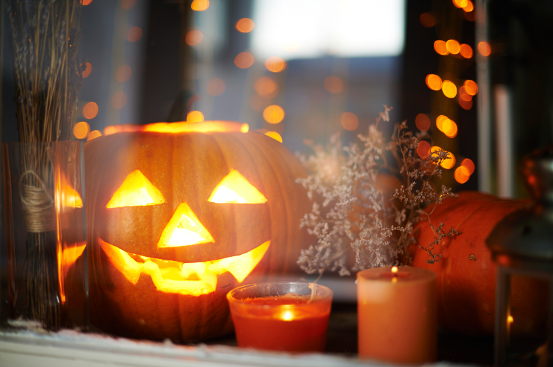 A Jack-O-Lantern Shines with Pillar Candles by the Window